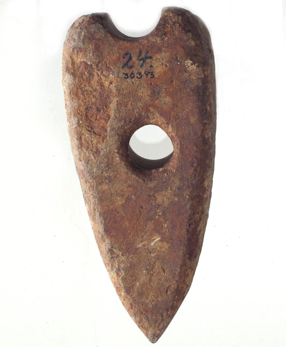 Skafthulløks av lys brunlig bergart, rimeligvis opprinnelig av typen H. Gjessing: Rogalands Stenalder, fig. 142, men med jevnbredt lengdesnitt. Avbrukket i det gamle skafthullet, et nytt boret nedenfor.
