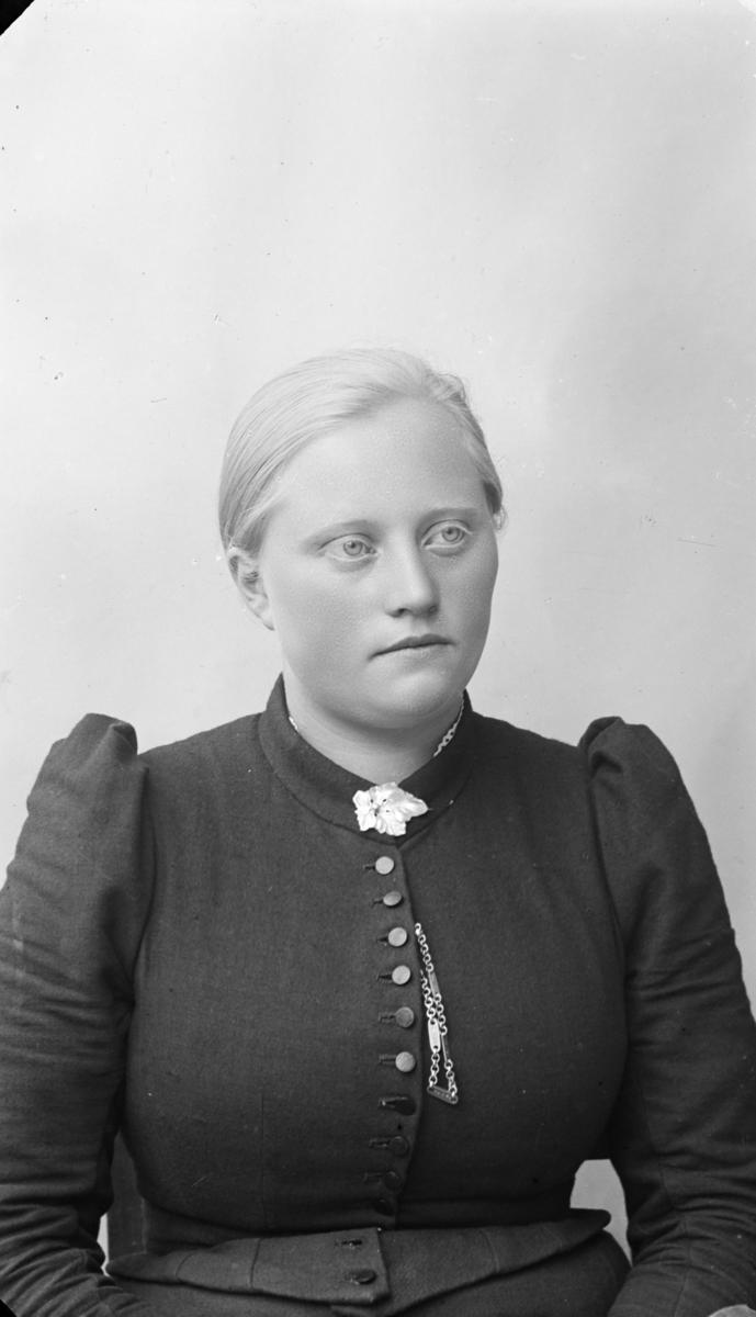 Portrett av yngre kvinne med lyst hår, kledd i mørk kjole med topp med knapping og puffermer, pyntet med kjede og halssølje