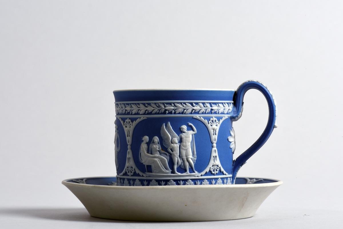 Kopp med fat av fältspatsporslin, wedgwood. Vit dekor i relief på blå botten, på fatet i form av bladbård och blommor. Koppen är dekorerad med bladbårder, även på örat, samt olika antika figurscener. Koppen har raka sidor och lätt svängt öra.