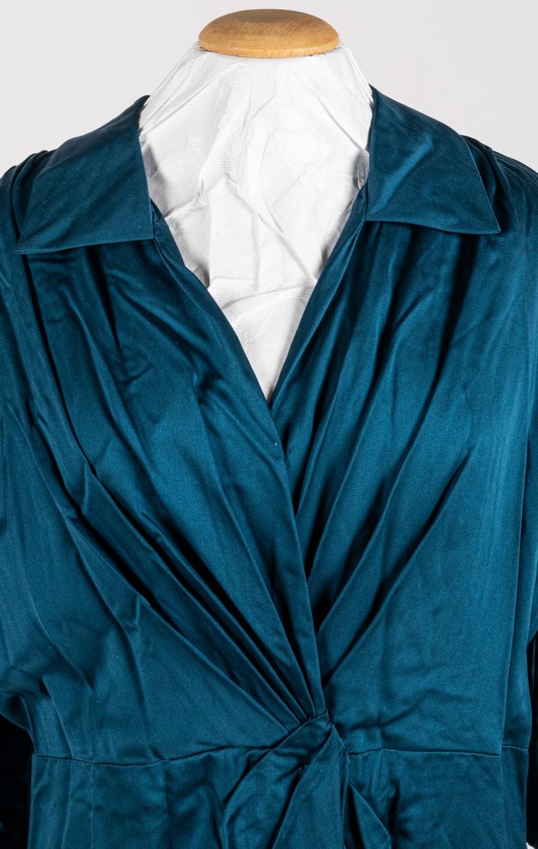 Klänning i blå bomulssatin. 3/4 lång ärm, krage, draperat framstycke, avskuren midja. Kjol draperad mot livet, veck bak. Dragkedja i sidan. Framstycket fodrat med nätliknande tyg. Konfektion eller sömmerskesydd.