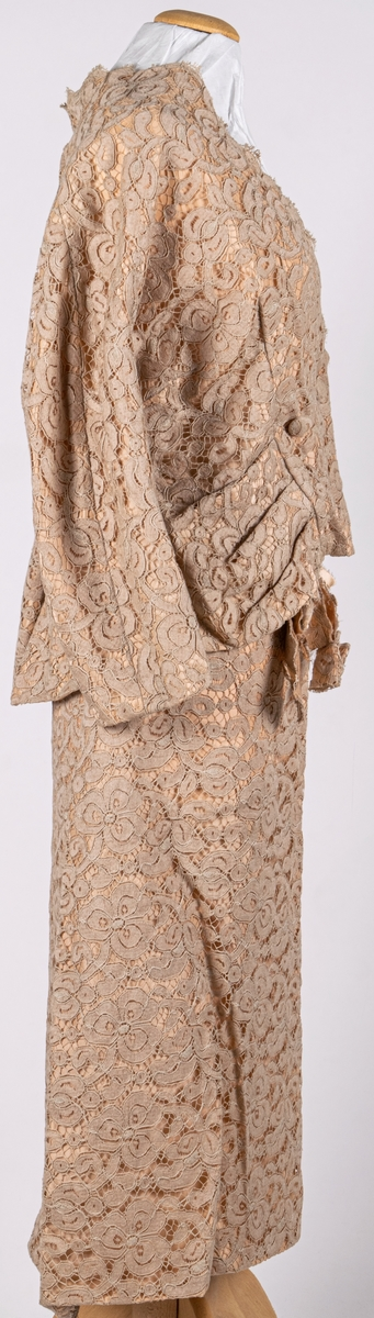 Tvådelad klänning (jacka och kjol). Beige, bomullsspets på gulrosa foder i duschess. Kort jacka med 3/4 lång kimonoskuren ärm. 2 stolpfickor fram. Kraglös med spestkanten som kantavslut. Omlottknäppning med 3 tygklädda knappar. Rak kjol med omlott fram. Dragkedja bak, knäppt med hyska och hake. Ewe-modell. Konfektion.
