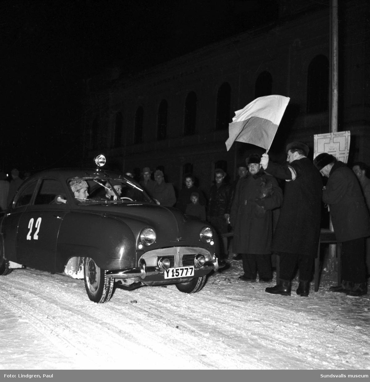 """Norrländska vinterrallyt i Sundsvall med 59 st startande. Bild 1 visar Gustaf Bergman, MAMK, vid ratten på sin Chevrolet, med E. Grane som kartläsare. På bild 2 ses startern Eric Ranbäck flagga av bilarna. Bild 3 visar vinterrallyts starkaste vagn, en öppen Jaguar """"här gäller det att vara påpälsad"""" med Oscar Swan, KAK, vid ratten och med Stig Lindström som kartläsare. Nattetappen går från Sundsvall till Åsele där en timmes uppehåll är obligatorisk. Dagsetappen går sedan till målet i Örnsköldsvik, dit även startande bilar från Skellefteå och Umeå anländer."""