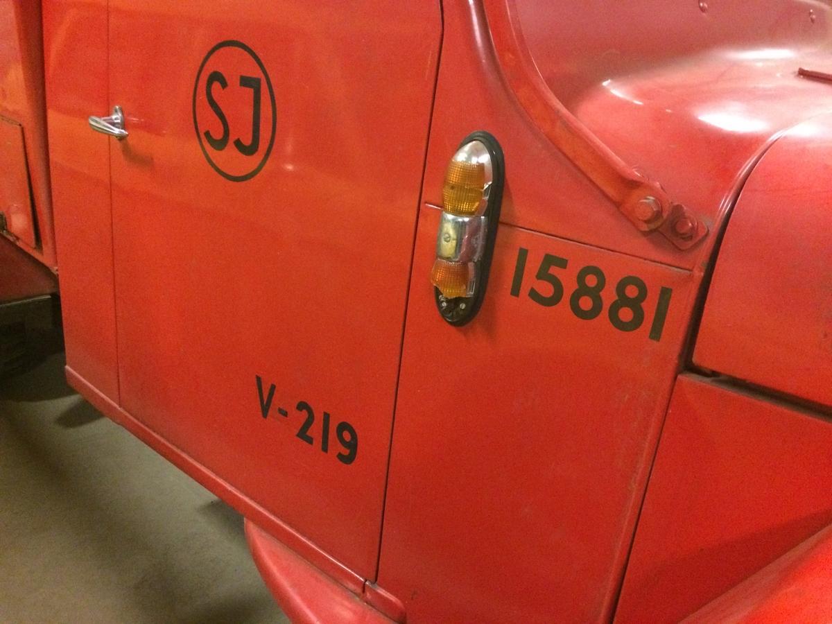 """Brandbil av Willys fabrikat. Öppen med vindruta och sidorutor. Sittbänkar på flaket klädda med röd galon. Extra däck samt två gröna väskor på flaket. Stegar ovanpå. Röd kaross. Märkt SJ i cirkel samt """"V-219"""" och """"15881"""" på sidorna. Hastighetsmätaren är graderad från 1 till 14."""