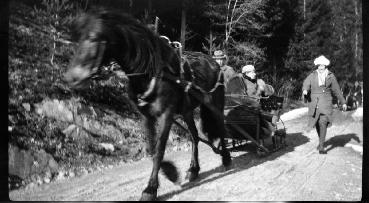Hest og slede, vinter. To personer i sleden og ei kvinne går ved siden av. Ca. 1920 - 30