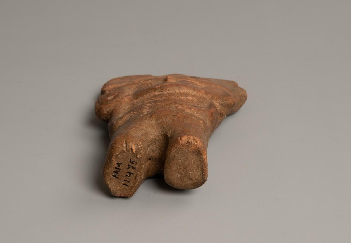 Mannsfigur.  Flat, med korte ben, flatt, bredt hode  m. store utbrettede ører eller hodeplagg. Et hull ved hver skulder  og ett i bakenden. Figuren er muligens hul.