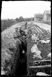 Tre män gräver avloppsdike