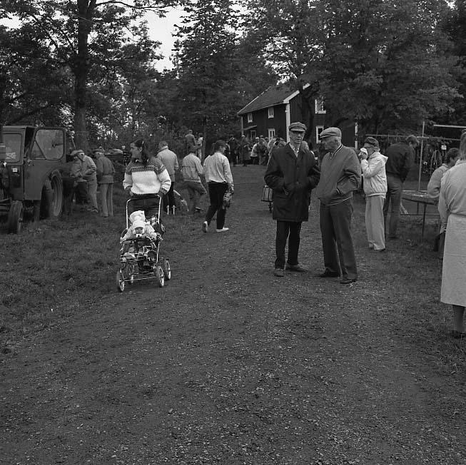 Auktion på okänd plats. Människor kantar en grusväg upp mot en bostad. En ung kvinna med barn i vagn promenerar mot fotografen.