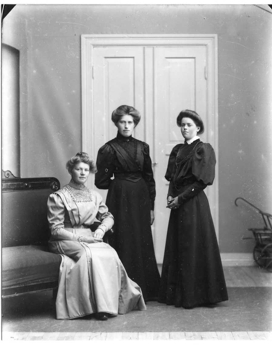 Gruppbild med tre i ljus respektive mörka klänningar. Kvinnan till vänster, i ljust, sitter på änden av en soffa och de andra står intill. Kvinnan till höger är Jenny Johansson från Örserum.