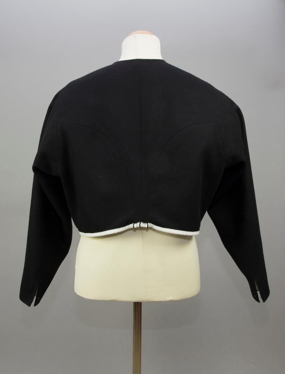 Kvinnotröja till vardagsbruk av svart kläde. Två fram- och sidstycken som går långt bak på ryggen med svängda sömmar mot två ryggstycken. Ryggstyckena smalnar av nedtill i ett minimalt skört med tre utstående veck. Nederkanten är uppvikt så att det vita fodertyget syns på utsidan. Ärmen är isydd och svängd med två sömma. Ärmsprundet knäppt med hake och hyska. Tät halsringning kantad med remsa av tyget. Tröjan knäpps kant i kant med 15 handjorda hakar och hyskor av mässings tråd, satta varannan hake varannan hyska. Foder av vit tuskaftat linne. Alla synliga sömmar, stickningar och fastsömnad av foder är sytt för hand. Ej synliga sömmar är sydda på maskin.
