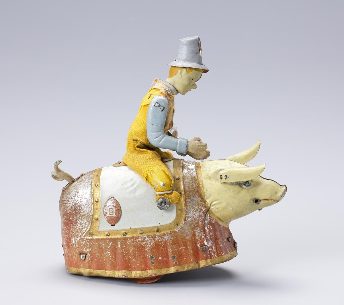 """Mekanisk leksak föreställande en figur med hatt (""""Dummerjöns"""", Bröderna Grimms sagor), sittande på en gris.  Genom ett fjäderverk inuti grisen vrider figuren ovanpå på överkroppen och grisen går fram och tillbaka i snäva svängar."""