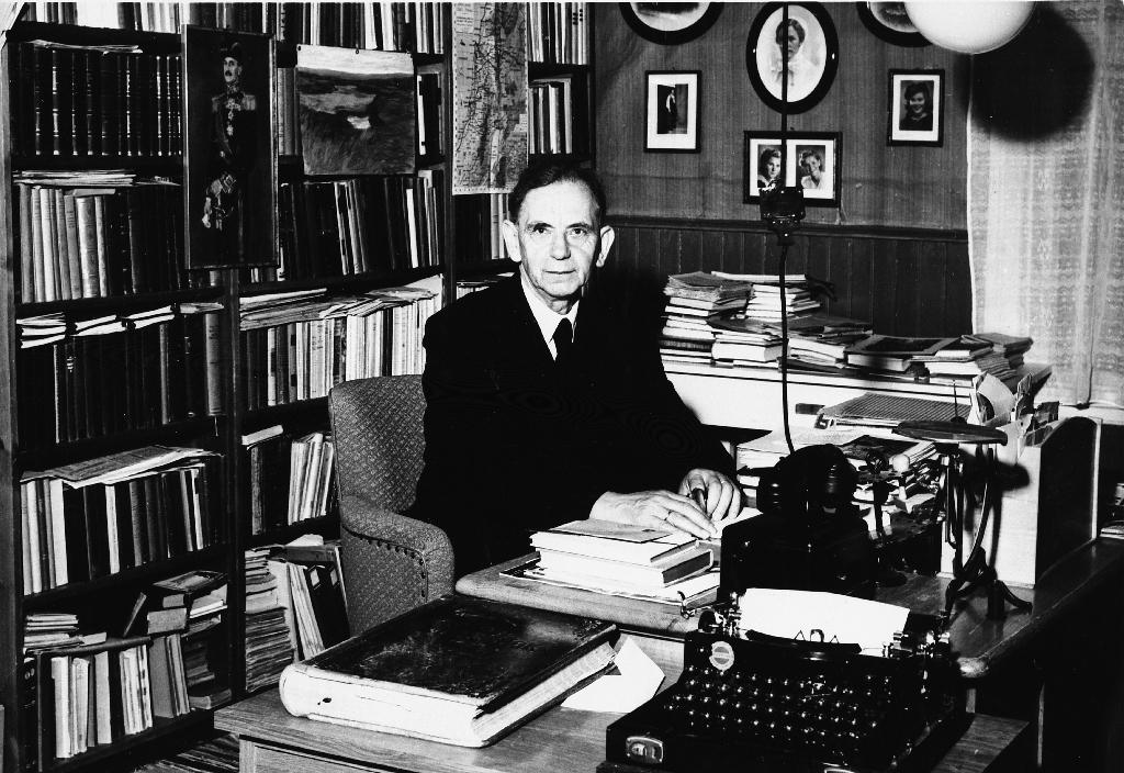 Prost Lars Tjensvoll ved skrivebordet i prestegarden i Volda på hans 70 årsdag 25.8.1958. Han var fødd på Tjensvoll i Time 25.8.1888, sokneprest i Nesna og Volda og prost på Sunnmøre.