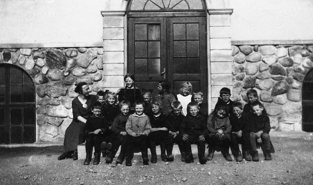 Elevar framfor inngangen til Bryne skule. Læraren, Dagny Tyse står til venstre.