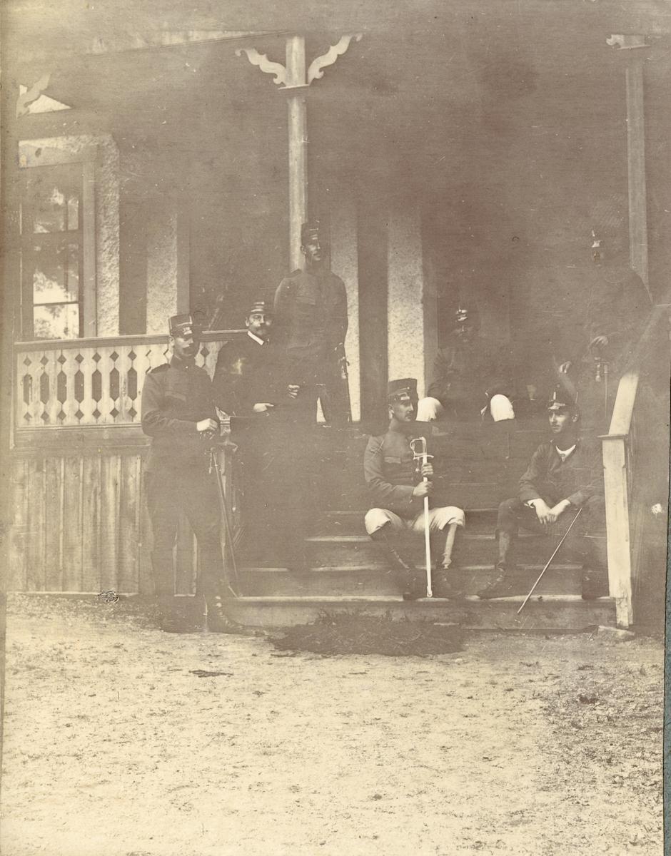 Officerare (Fortifikationen?) sitter på trapp utanför byggnad.