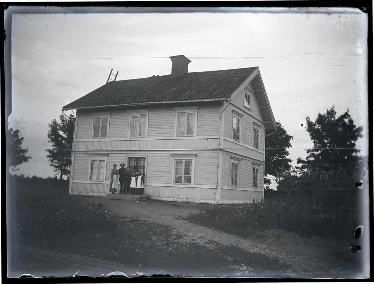 Par med tre barn, stående på trappa till hus.