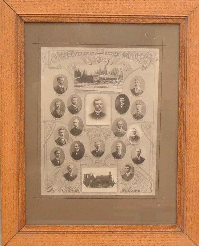 Tavla med porträttsamling eller kollage, i ljusbrun träram och glas. De 18 porträtten är ovala, och visar deltagare vid SJ:s lokeldarekurs i Boden 1909. Kompositionen består av ett arrangemang av porträtt av tjänstemän samt två fotografier av ånglok. Överst ett bevingat hjul.