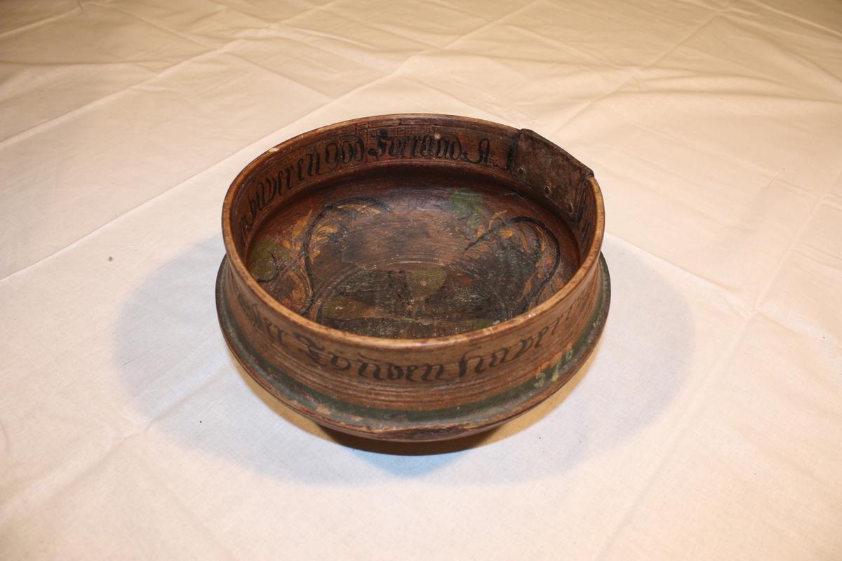 Dreia ringar på utsida. Utsida er brunmåla med grøne ringar. På innsida er det bladrankar, rose og blad i gult, grønt og svart på brun botn.