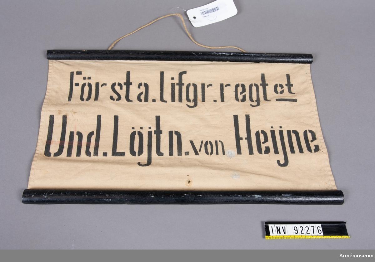 """Tygskylt fäst mot två svartmålade träribbor. Tryckt text: """"Första Lifgr.regt:et Und. Löjtn. von Heijne""""."""