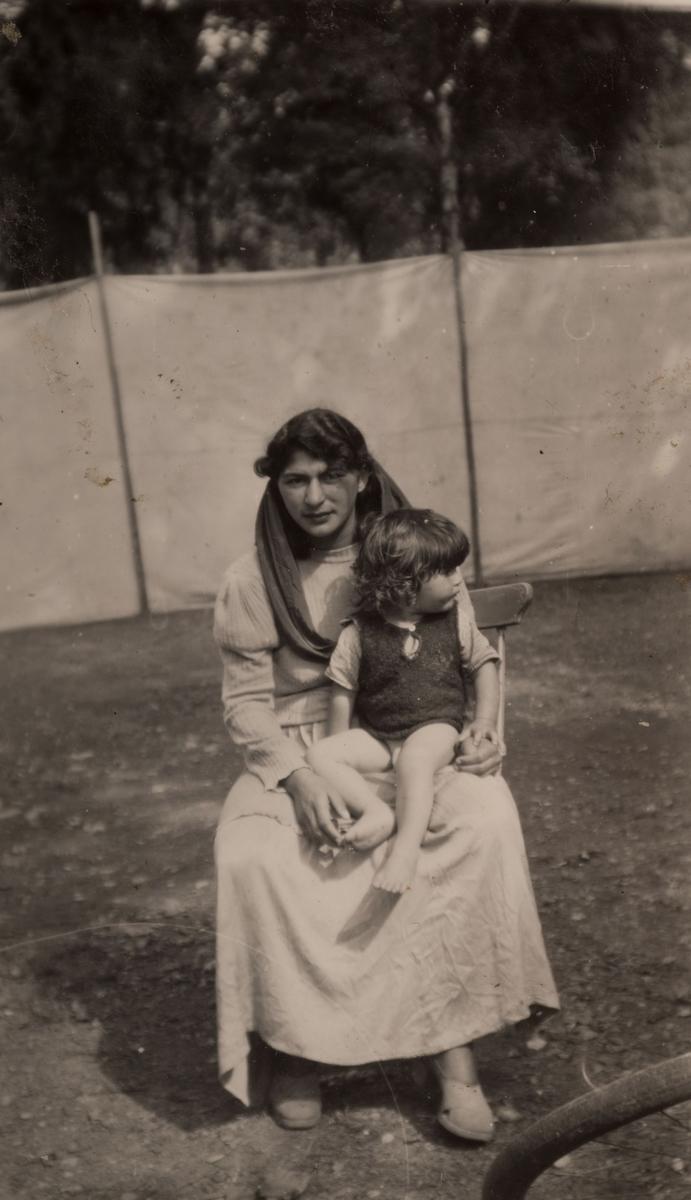 Romsk kvinna sitter med sin dotter i knät, Storvik den 27 juli 1950. I bakgrunden syns en uppspänd tältduk som används för att hålla obehöriga besökare utanför lägret.