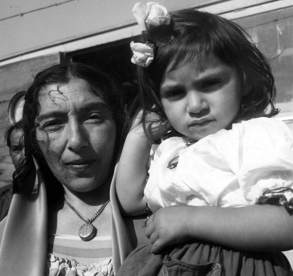 Romsk kvinna håller ett barn i famnen. Toleransen för romer har historiskt varierat mycket mellan olika samhällen, men romers närvaro har sällan setts som något positivt. Ofta fick man slå sig ned i samhällets utkant, man har förvägrats fast bostad och fördrivits. Efter att de svenska romerna i Sverige erkändes som medborgare år 1952 uppstod debatt kring gruppens svåra levnadsförhållanden. En statlig utredning genomfördes under 1954-1956 där en av slutsatserna blev att fast bostad var nyckeln till att lyckas med skolgång och arbetsliv. Från och med mars 1960 hade möjlighet att rekvirera statsbidrag för kostnader i samband med romers bosättning, vilket förenklade möjligheten för svenska romer att få tillgång till permantenta bostäder samt i förlängningen studier och arbete.