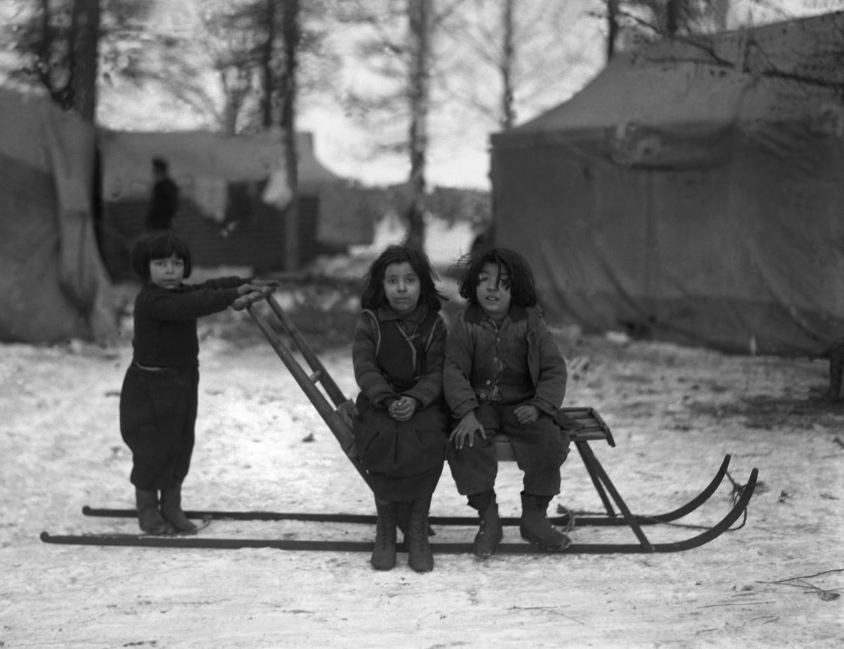 Tre romska barn sitter på en sparkstötting. I bakgrunden syns tälten i lägret. Svenska romer har historiskt tvingats bo i läger, ofta i samhällets utkant, då man har förvägrats fast bostad och fördrivits. Toleransen för romer har varierat mycket mellan olika samhällen, men romers närvaro har sällan setts som något positivt. Efter att de svenska romerna i Sverige erkändes som medborgare år 1952 uppstod debatt kring gruppens svåra levnadsförhållanden. En statlig utredning genomfördes under 1954-1956 där en av slutsatserna blev att fast bostad var nyckeln till att lyckas med skolgång och arbetsliv. Från och med mars 1960 hade möjlighet att rekvirera statsbidrag för kostnader i samband med romers bosättning, vilket förenklade möjligheten för svenska romer att få tillgång till permantenta bostäder samt i förlängningen studier och arbete.