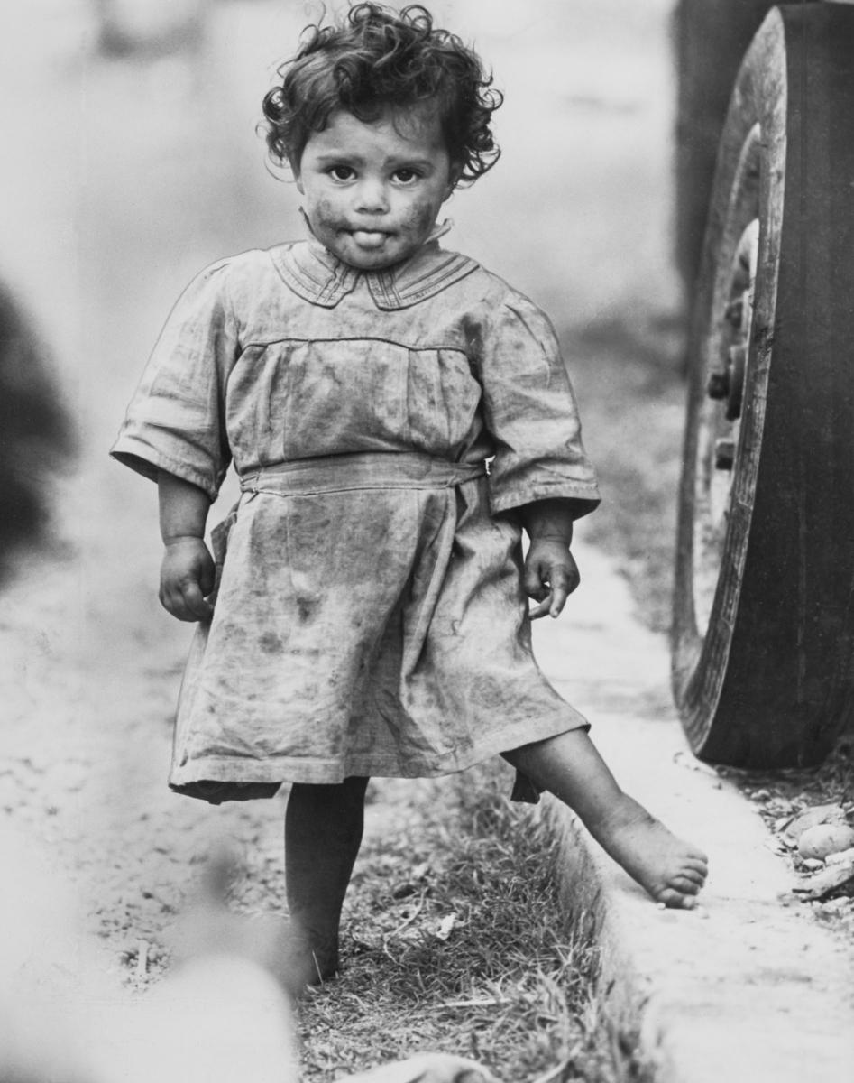 En liten romsk flicka står vid en bil. Hon tittar rakt in i kameran. Bilden är tagen i Saintes-Maries-de-la-Mer i Frankrike år 1947. Enligt en legend finns här kvarlevorna efter romernas skyddshelgon Sara e Kali (Svarta Sara) och staden har blivit en pilgrimsort för många romer. Sara e Kali har aldrig fått helgonstatus av katolska kyrkan, men varje år den 24e maj helgas hon med en speciell ritual. Enligt legenden ska Sara e Kali varit tjänarinna till de tre Marior som staden är döpt efter: Maria Magdalena, Maria Jacobea, som var syster till jungfru Maria, och Maria Salome, som var mor till apostlarna Jacob och Johannes. Huruvida denna bild har någon koppling till stadens roll som pilgrimsort för romer är okänt. Toleransen för romer har historiskt varierat mycket mellan olika samhällen, men romers närvaro har sällan setts som något positivt. Ofta fick man slå sig ned i samhällets utkant, man har förvägrats fast bostad och fördrivits. En stor del av den romska befolkningen i Europa dödades av nazisterna under andra världskriget och efter kriget levde många på flykt. I Frankrike förvisades många till speciella gettoliknande områden och förnekades arbete. Från 1914 hade Sverige ett inreseförbud för romer, men efter att det upphävdes år 1954 flydde många romer till Sverige. Under 1960-talet kom detta att föranleda en stor politisk debatt.