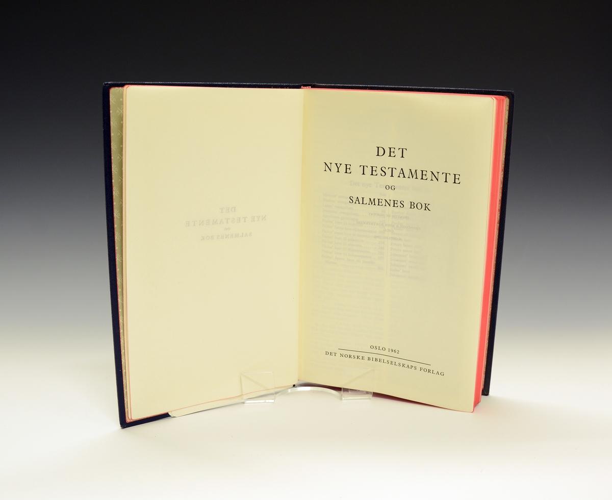 Det nye testamentet og Salmenes bok i blå shirting med gullbokstaver.