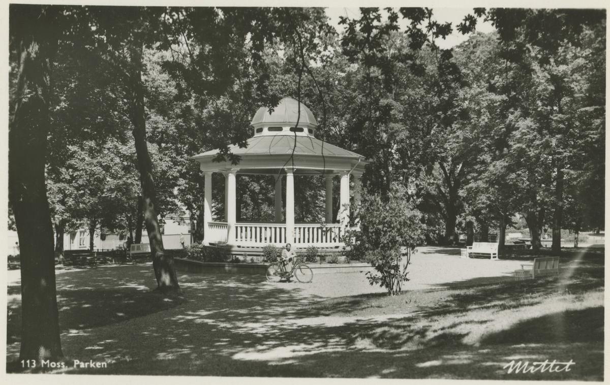 """Kirkeparken. 1947. Mittet. Fotograf har stått i kirkeparken. Musikkpaviljongen, dame med sykkel. Historikk:Paviljongen ble oppført til byjubileet i 1920.   Tekst: """"113 Moss Parken"""", """"Mittet""""."""