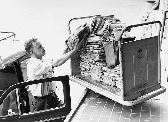 Lokalbrevbärare i Farsta 1965. Med anledning av personalbrist vid postkontoret Farsta 1, måste brevbäraren använda sin egen bil som depå för buntarna. Det saknades personal för att köra ut posten till brevbäringsdistriktens avbuntningslådor.