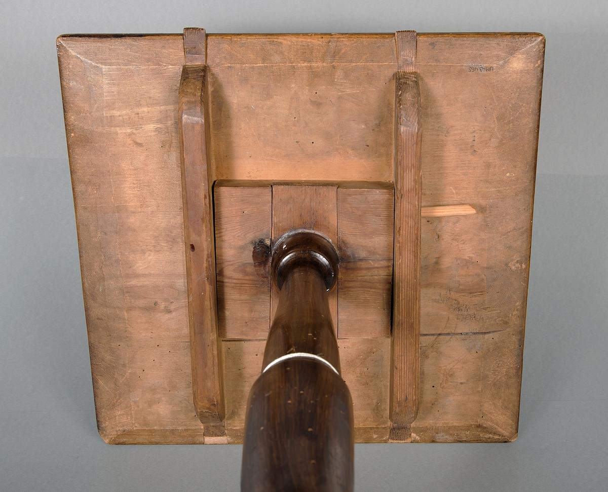 Bord. Pelarbord med tre ben och rektangulär, fällbar skiva. foten rund, svarvad. Skivan låses fast med plugg av trä (sannolikt inte original). Skivan fläckig och nött. I ena hörnet inristat en bokstav, möjligen H. Två stycken. Bordet är brunlaserat. Fötterna utformade så att det ser ut som klossar fästa under.