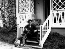 Doktor Otto Mejlænder sitter på trappa med hund.