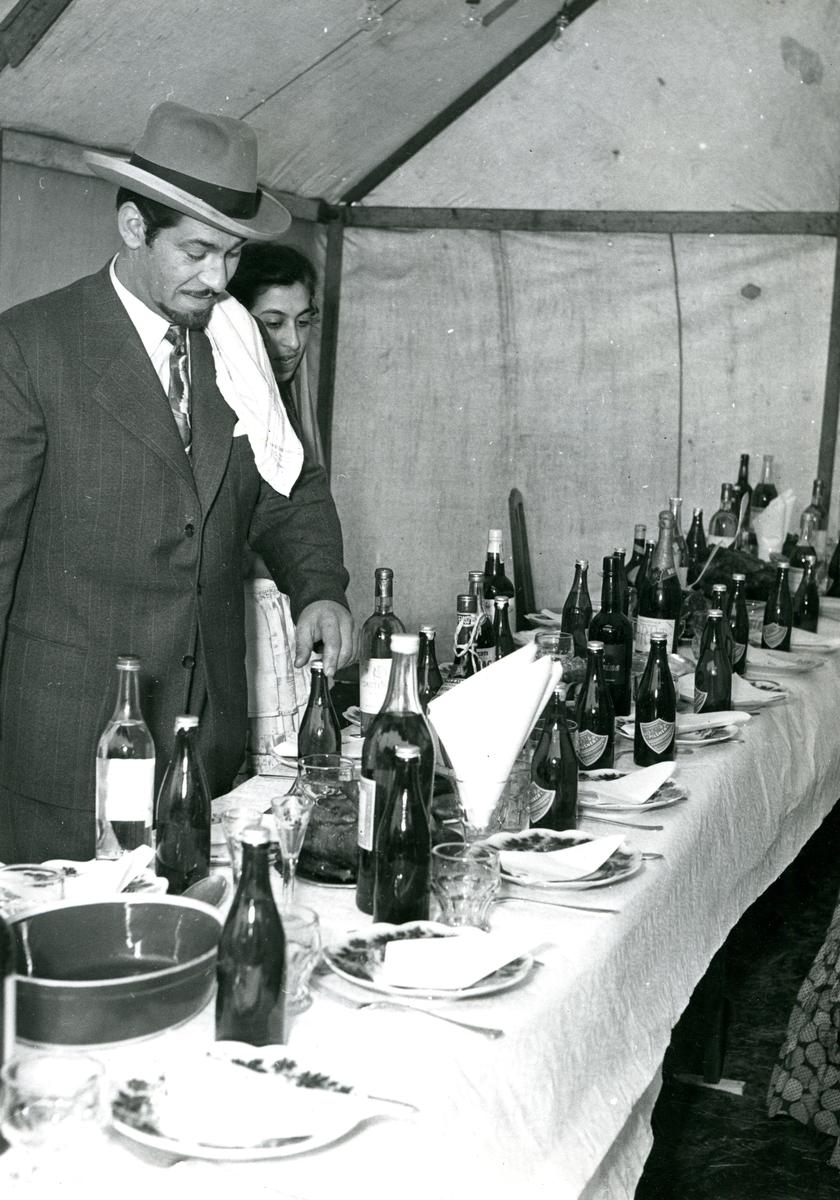 I ett tält är ett bord uppdukat för fest. Under 1900-talet har svenska romer inte tillåtits bli bofasta, utan hänvisats att slå läger i samhällets utkant. Hur länge man fick stanna på en plats var olika från kommun till kommun, men praxis verkar ha varit tre veckor. Efter att de svenska romerna erkändes som medborgare år 1952 uppstod debatt kring gruppens svåra levnadsförhållanden. En statlig utredning genomfördes under 1954-1956 där en av slutsatserna blev att fast bostad var nyckeln till att lyckas med skolgång och arbetsliv. Från och med mars 1960 hade kommuner möjlighet att rekvirera statsbidrag för kostnader i samband med svenska romers bosättning, vilket förenklade möjligheten att få tillgång till permanentbostad, studier och arbete. Denna process kom dock att bli utdragen under flera år.