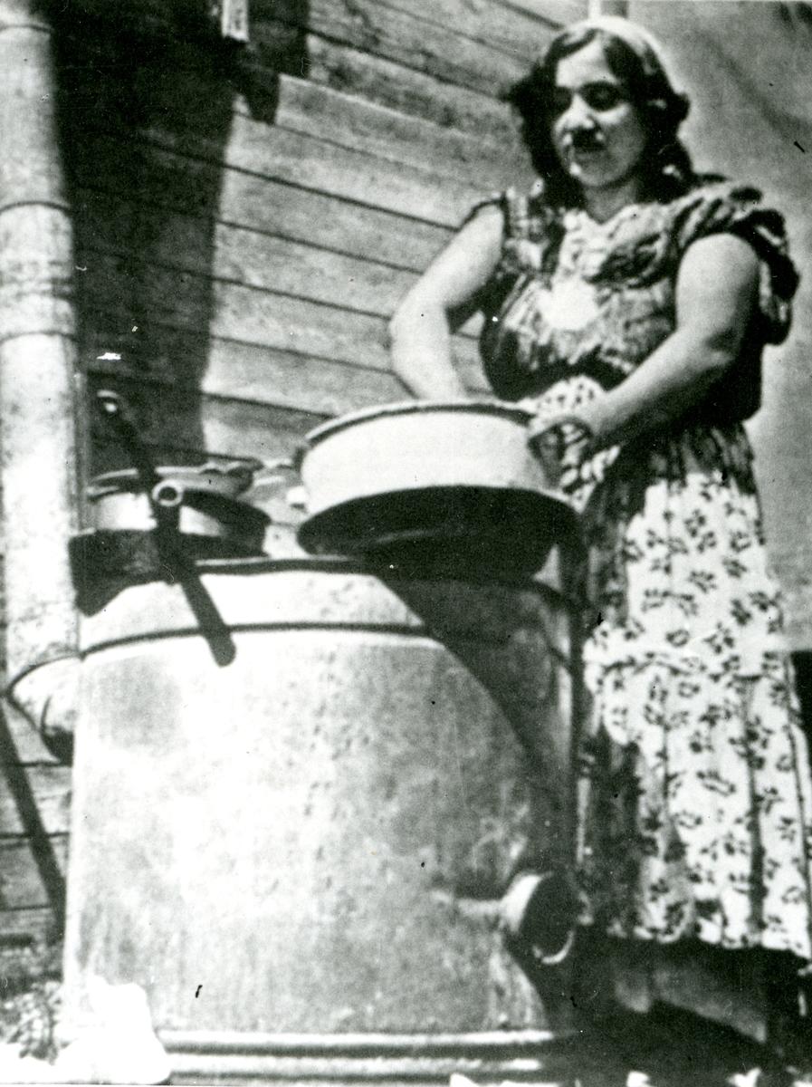 En ung kvinna står framför en yttervägg och diskar. Bildens ursprung är okänt.