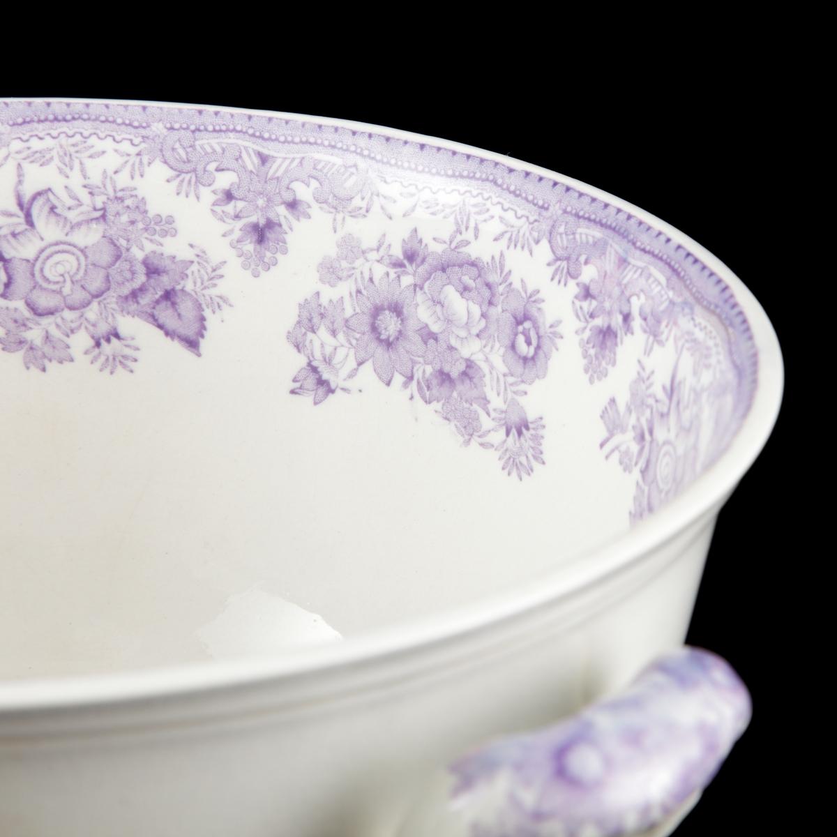 Rund skål med två öron och låg, konisk, insvängd fot. Locket välvt med svagt klockformig profil, bredare än skålens mynning, knopp i form av blomknopp och hål för soppslev. Dekor i ljust violett, blommönster och fasaner.