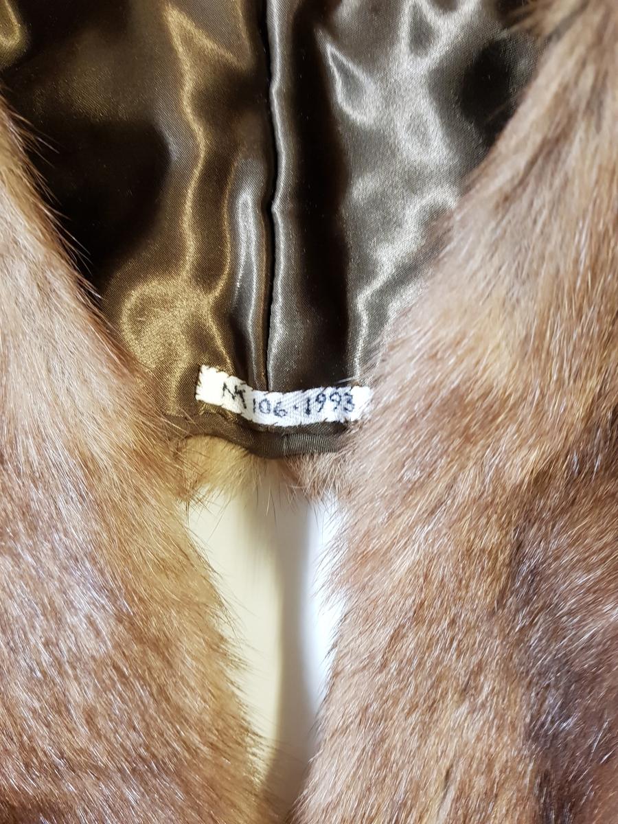 Midjelang stola, som kan lukkes med én kraftig hekte midt foran. Ved halsåpningen er skinnet splittet, slik at det fremkommer en effekt av et legg rundt nakken, med en ytre del som rager litt høyere enn det smalere stykket innerst mot halsen. Øvre del har søm midt bak, og skinnet er brettet inn mot nakken. På grunn av splitten som er skåret på hver side av nakken, dannes det et skrått skulderparti. Nedenfor skuldrene er det skjøtt på lange, jevnt brede og avrundede forstykker.  Plagget er fôret, og har en stor fuktskjold på den ene siden. Fôret er av blank, myk, silkeaktig sateng, men kan kanskje være sekundært og av syntetfiber. Ingen spor etter etikett. Pelsverket er fra dyrets ryggstykke, og er anvendt slik at den mørke stripen fra ryggstykket danner et dekorativt element.