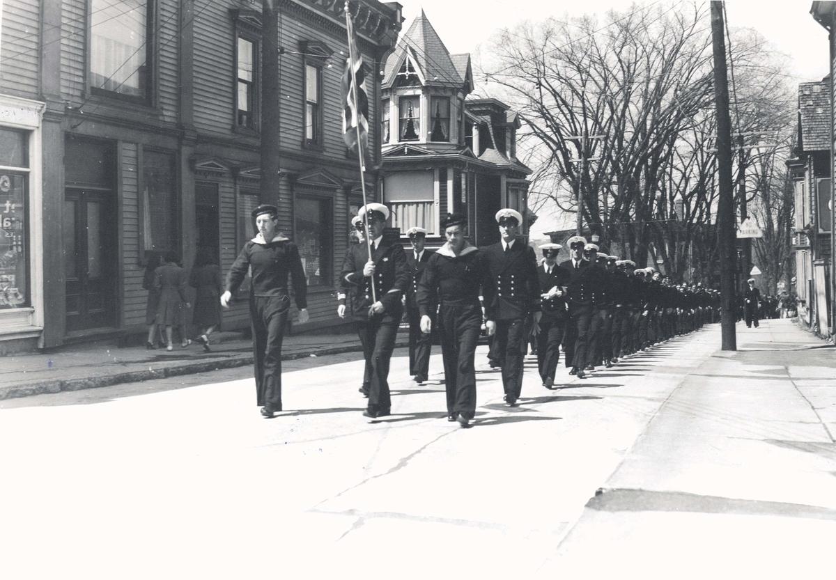""""""" Camp Norway"""", Lunneburg, Nova Scotia. Befal og menige marsjerer med norsk flagg."""
