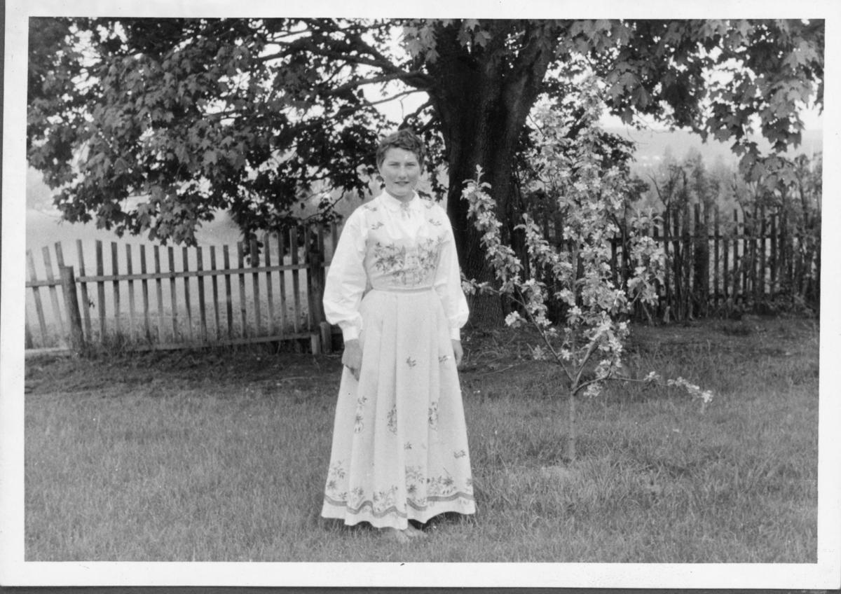 Kvinne i Lundebybunad i hage med blomstrende epletre, trolig etter andre verdenskrig.