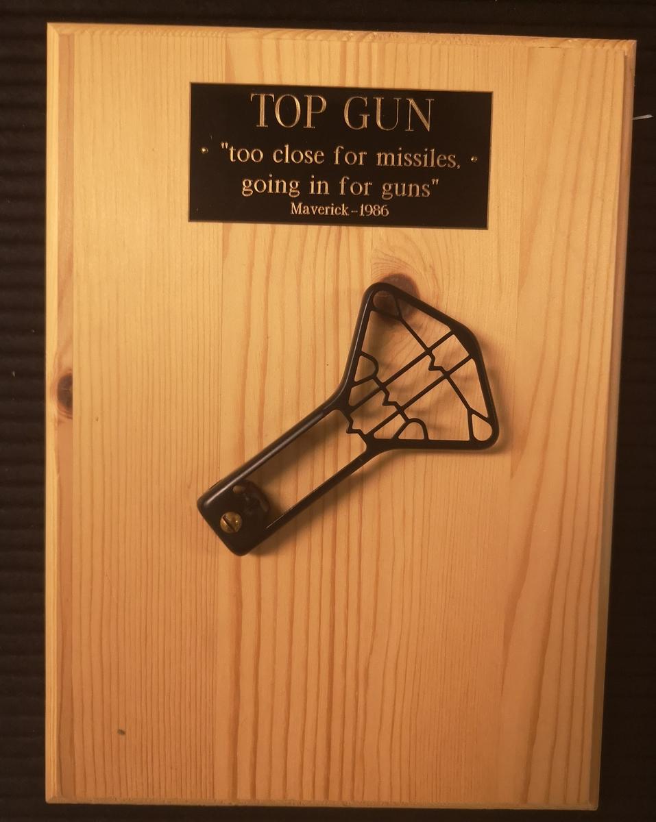 """Treplate med textplate og text: TOP GUN """"too close formissiles, going in for guns"""" Maverick-1986."""