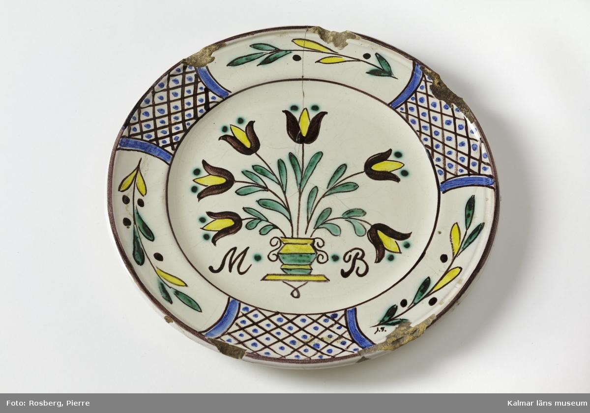 KLM 45169. Tallrik, barntallrik. Av keramik, fajans, gul skärv. Med brätte, något skålat. Motiv med blomsterurna i centrum, brättet täckt med dekor, kvistar med blad samt partier med rutmönster. I färgerna ametist, grönt, gult och blått mot vit bakgrundsfärg. Bokstäverna M och B på var sin sida om urnan. MB, står för Märta Brütte. Signerad på framsidan, på brättet: J.S., står för John Sjöstrand. Tillverkad vid Sandbäcks kakelfabrik. Flera nagg utmed kanterna samt spricka, äldre skador.