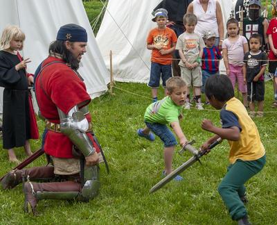 Ridder i middelalderdrakt og delvis rustning kneler mens han instruerer to gutter til å slåss med sverd. (Foto/Photo)