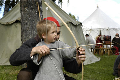 Bueskyting er populær middelalderaktivitet, her err det en liten gutt som får hjelp av en voksen mann til å spenne buen, begge har på seg enkle middelalderklær, og det står middelaldertelt i bakgrunnen.. Foto/Photo