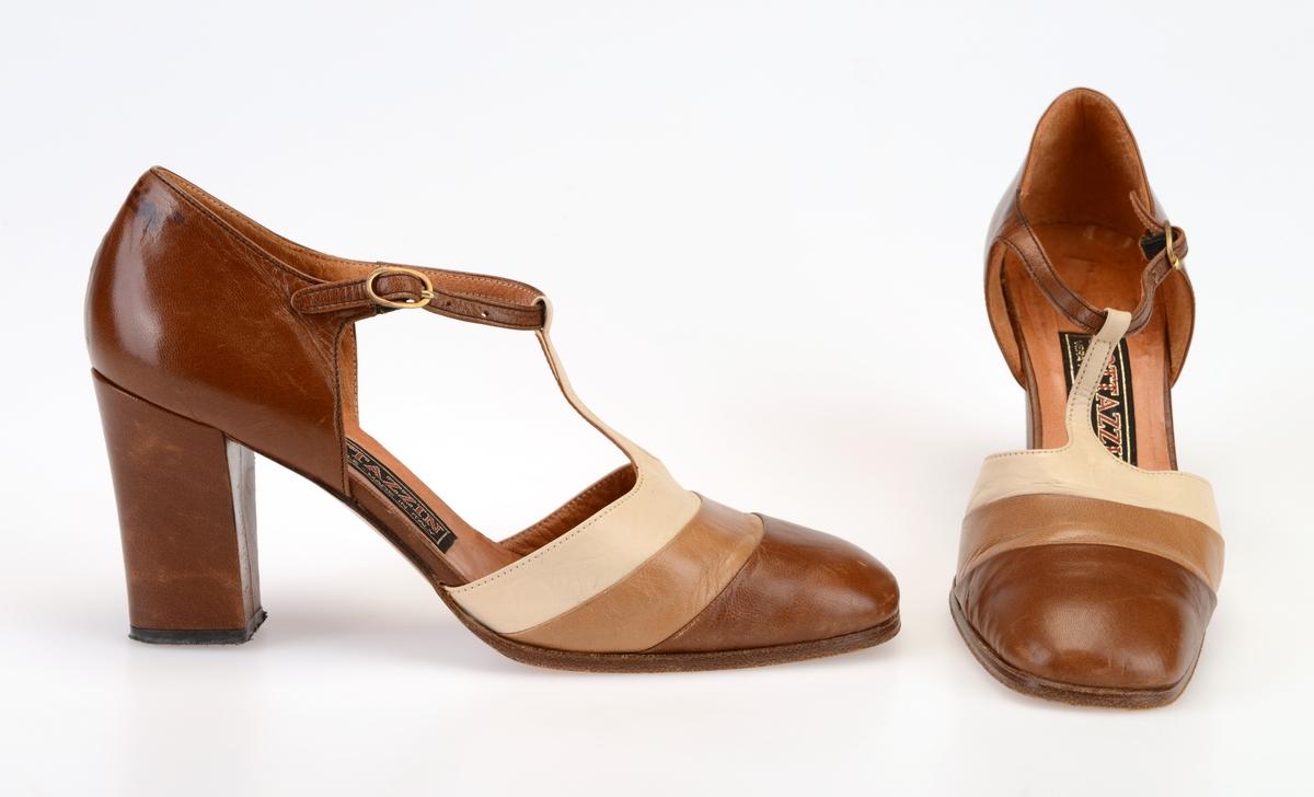 Et par høyhælte skinnsko til dame. Tåen er avrundet med noe firkantet form. Foran er skoen i brunt, beige og hvitt skinn. Det går en hvit skinnreim opp til ankelreimen så det dannes en T-reim. Skoen er åpne på sidene. Hælkappen er av brunt skinn og er avstivet. Ankelreimen er av brunt skinn og festes med gullfarget metallspenne. Det er tre hull for stramming. Innersålen er av lyst brunt skinn. På sålen er det limt på en etikett med tekst. Skoen er foret med lyst brunt skinn i den remre delen av skoen. Yttersålen er av brunt lær, men på hælen er det svart plast. Hælene er tykke og høye.