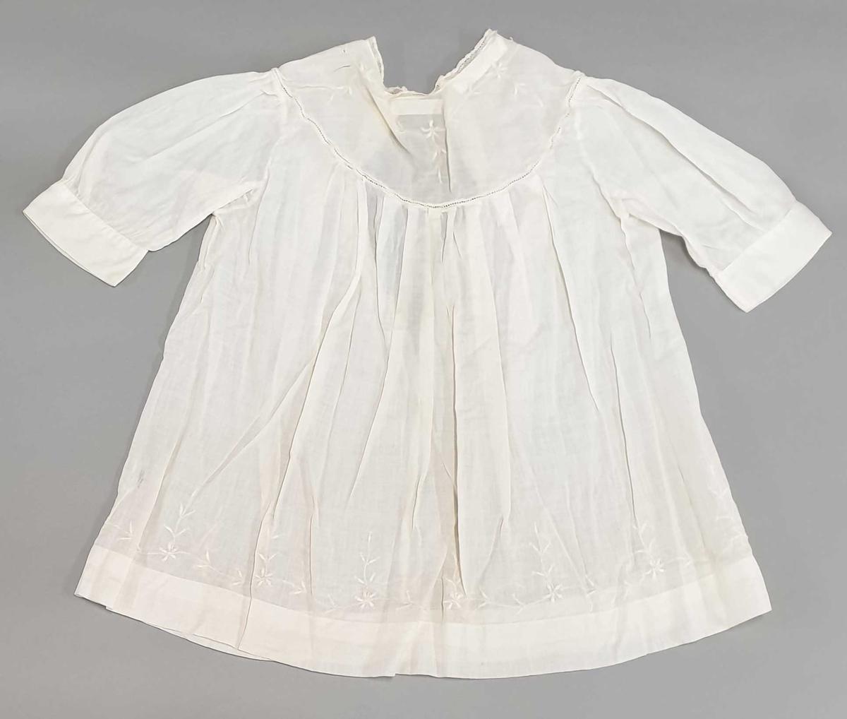Hvit nesten transparent bomullskjole med broderi langs halskanten, lange ermer og knyting i halsen.