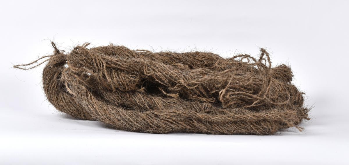 """En hespel har to-tråds garn spunnet av grisebust og hestetagl. 11 slike hespler er festet sammen i en bunt.   Om veven som er rent med garn av bust: """"Veven står oppsatt med vevnad til """"Tjone-håre"""". Renninga er garn av hestetagl og kurompe. Veften (islett) er garn spunnet av grisebuster.  Å spinne garn av tagl og grisebust var engang meget almindlig. Garnet bruktes ikke bare til å veve tjonehåre av. (Tjonehåre var det som man tørket kornet på.) Men tagl og bustegarn bruktes mye til julingsreip og kjøretømmer på hestene. Disse kjøretømmene sleit hardt på vottene. Men de blev aldri våte. De var tørre støtt, sa de gamle. """" Fra protokollen."""