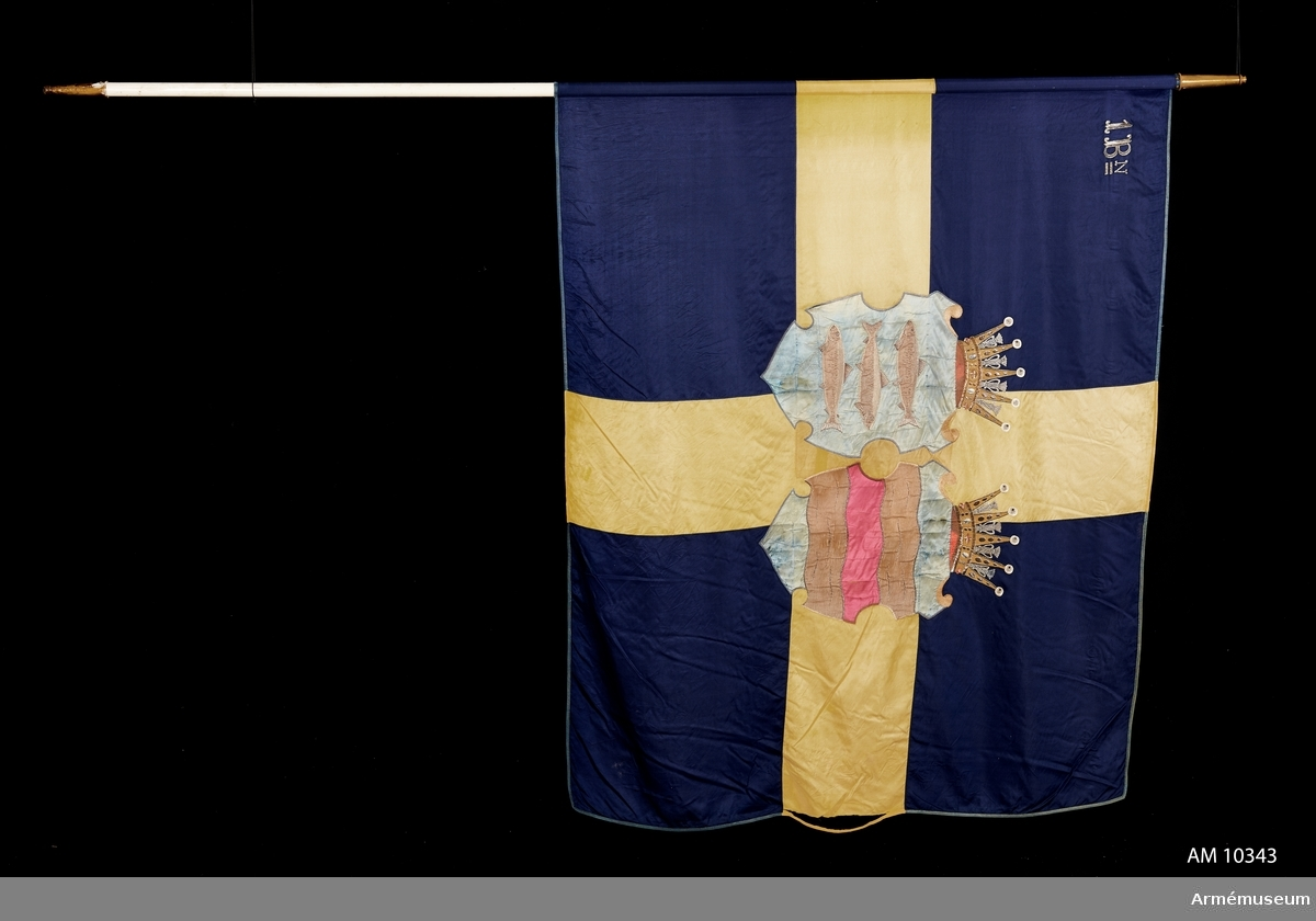 Grupp B I. Duk av blått och gult siden med Västernorrlands heraldiska vapen bestående av Ångermanlands och Medelpads vapen i varsin sköld krönta med hertigkronor. I övre stångsidan broderat 1 Bn (första bataljonen)   Samhörande: Spets, kravatt och fodral. Överlämnad jämlikt Go 3596/1951.