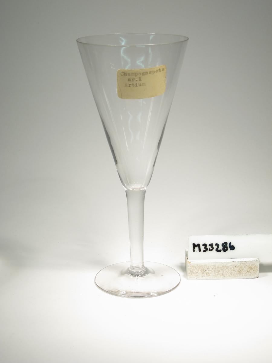 """Champagneglas med konformad kupa och påklippt ben. Lapp: """"Champagnespets Nr. 1 Artium"""""""