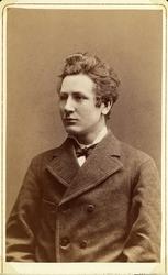 Foto av en ung man i tweedjkavaj, stärkkrage och fluga. Midj