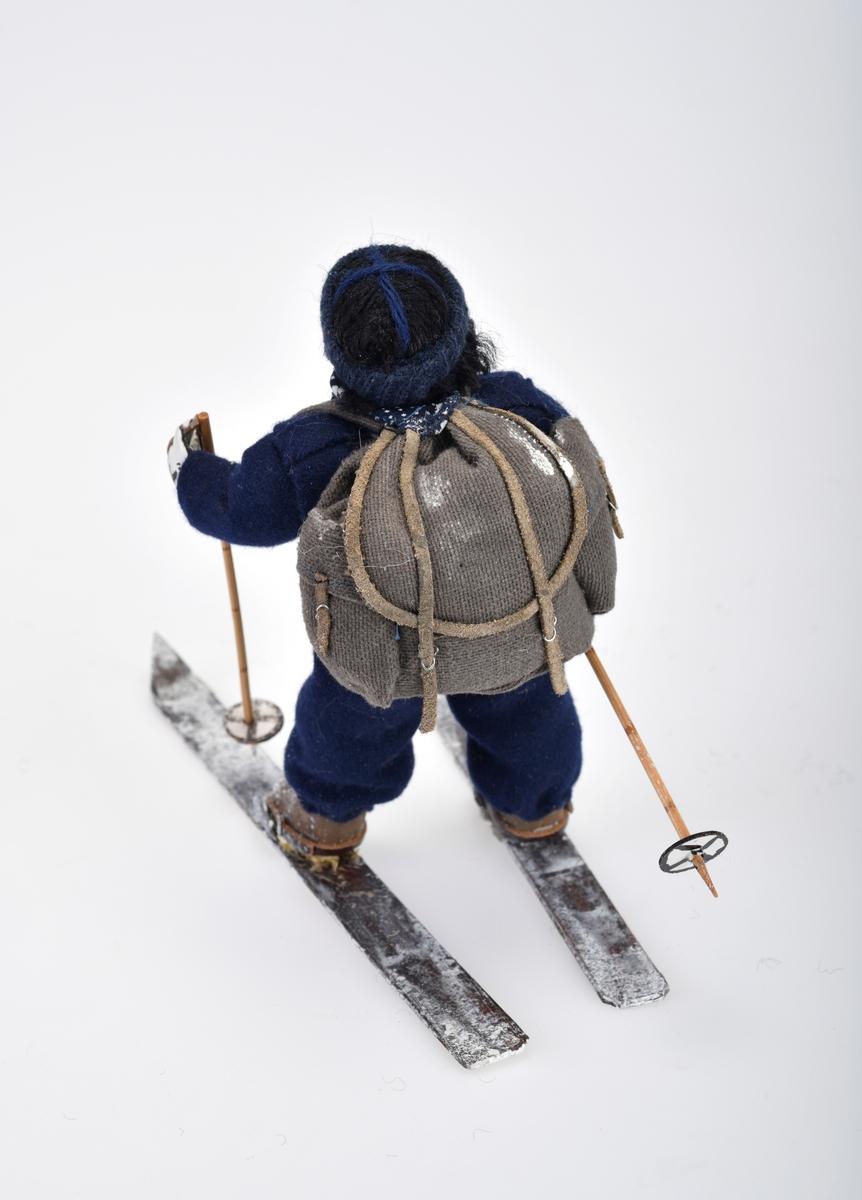 Liten damefigur med ryggsekk, ski på beina og skistaver i hendene.