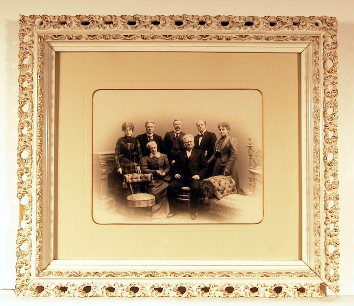 Familieportrett: mor og far sitter i stoler foran, bak i midten de tre sønner, og de to døtre på hver sin side innrammer bilde. Alle ser direkte på betrakteren.