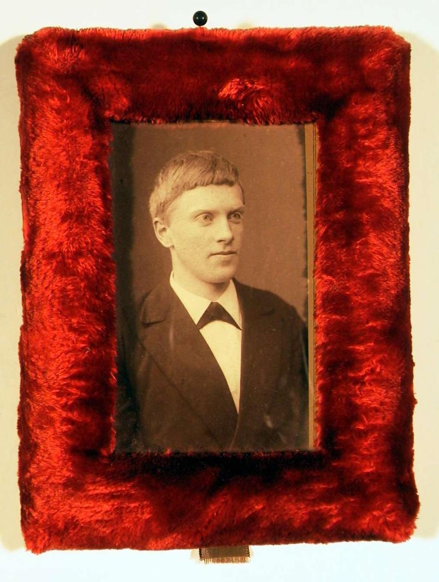 Portrettfotografi av ung mann i mørk dress med hvit skjorte med mørkt halsbind.