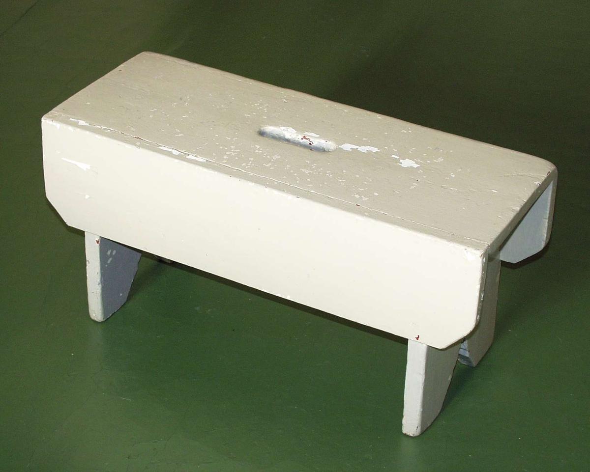 Kraftig gråmalt skammel. Setet har utskjering til håndtak. Fotstykket utskåret i profilert trekant. Rett sarg på sidene, avskåret ved fotstykket.